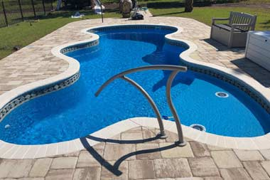 The Desert Falls is a fun and lavish fiberglass swimming pool with a wild free form pool shape. It sports a 6' deep end and a standard hopper with a gradual slope from the shallow end. As seen in this image, the shallow end includes a wide tanning ledge (shown here with two bubblers).