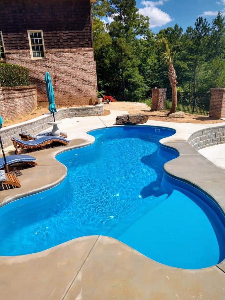 "The Desert Falls is a fun and lavish fiberglass swimming pool with a wild free form pool shape. It sports a 6'  1.25"" deep end and a standard hopper with a gradual slope from the shallow end. As seen in this image, the shallow end includes a wide tanning ledge (shown here with two bubblers)."